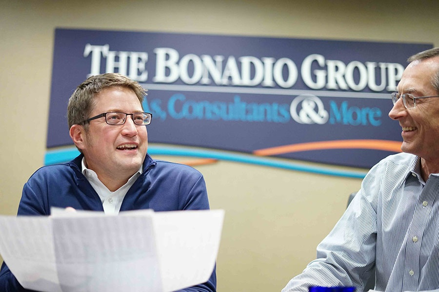 John laughing in front of The Bonadio Group sign