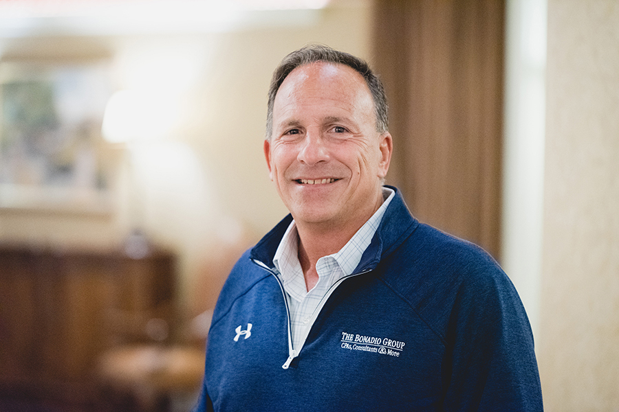Thomas Giglio wearing a navy blue quarter zip with a blue and white shirt